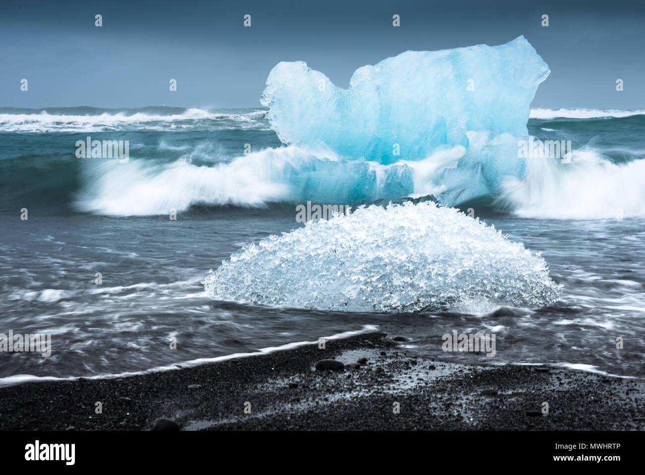 longexposure image of two icebergs at Diamond Beach at Jökulsárlón - Stock Image