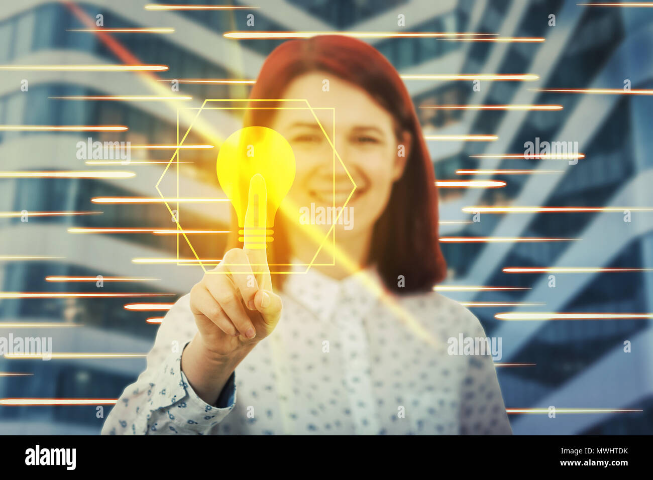Smiling woman touching digital screen interface with her finger. Press a golden light bulb. Creativity and idea concept in the modern virtual technolo - Stock Image