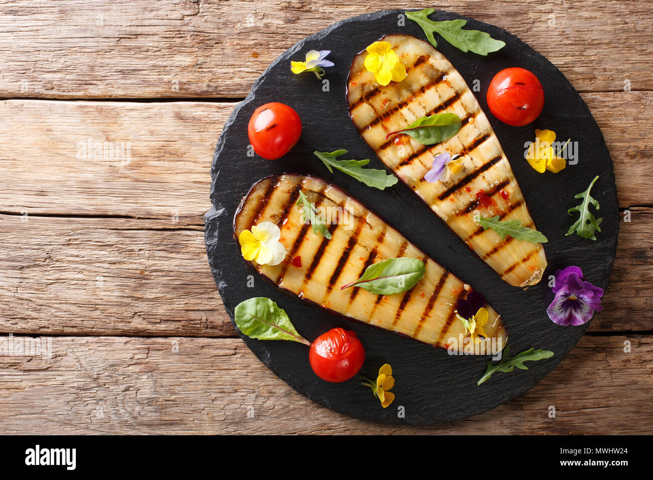 Portion of grilled eggplant and tomato with herbs and edible flowers close-up on the table. horizontal top view from above - Stock Image