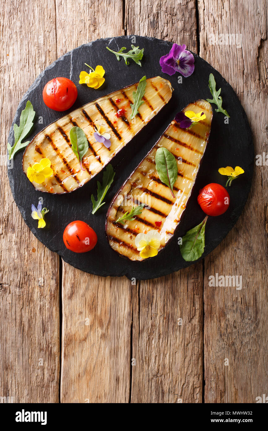 Portion of grilled eggplant and tomato with herbs and edible flowers close-up on the table. Vertical top view from above - Stock Image