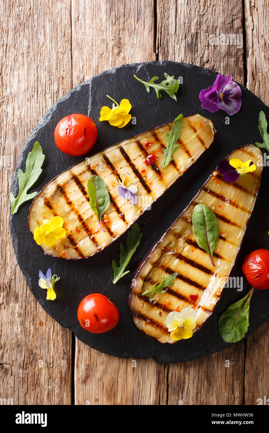 Organic food: grilled eggplant and tomatoes with herbs and edible flowers close-up on the table. Vertical top view from above - Stock Image