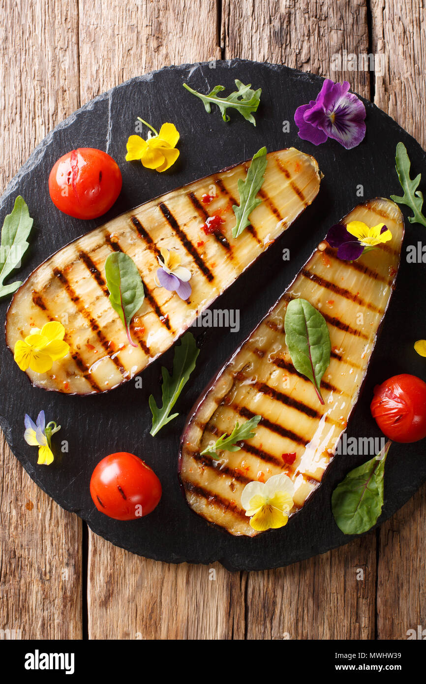 Summer appetizer from grilled eggplants and tomatoes with herbs and edible flowers close-up on the table. Vertical top view from above - Stock Image