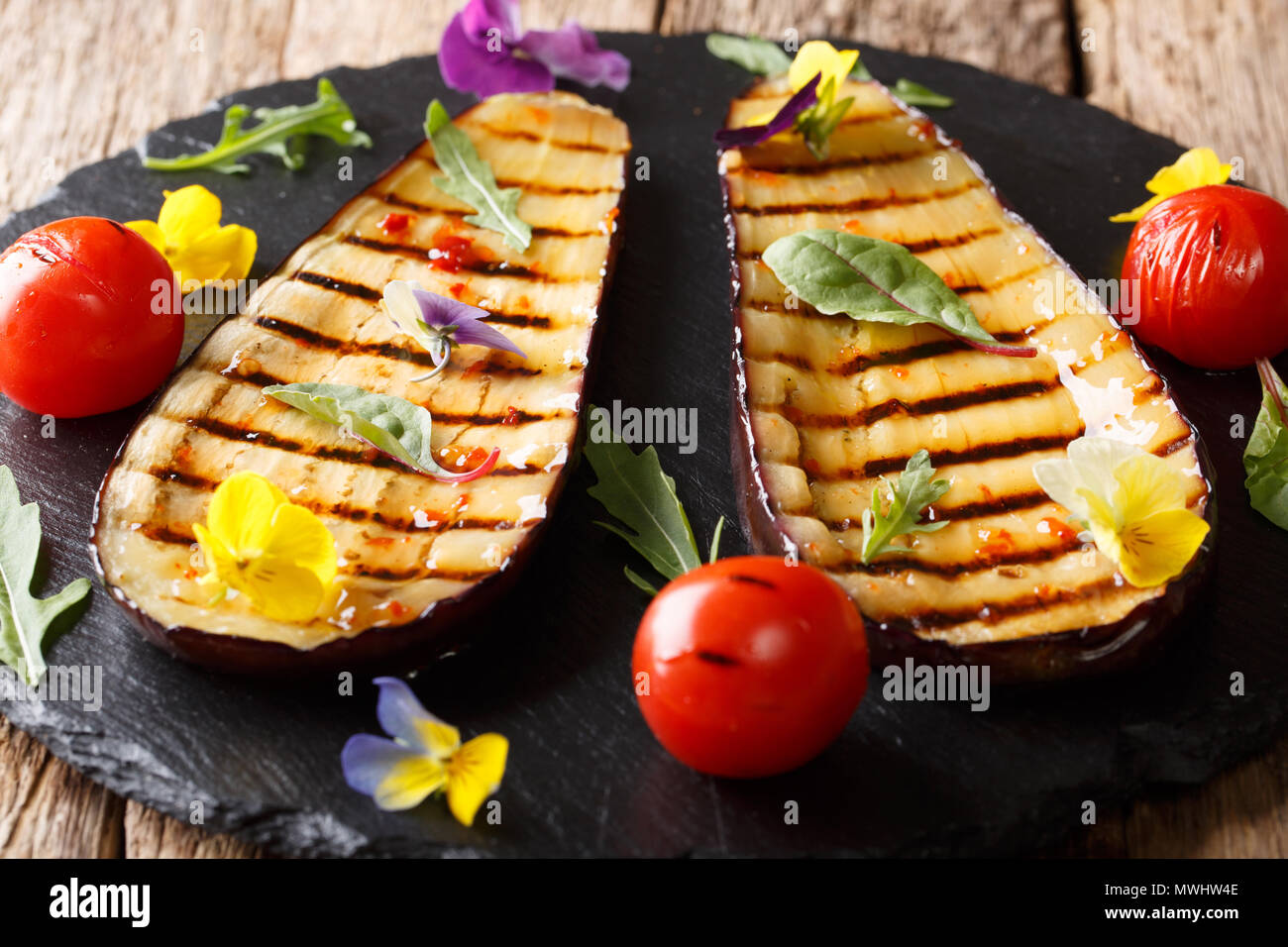 Grilled eggplant and tomatoes with herbs and edible flowers close-up on a platter. horizontal - Stock Image