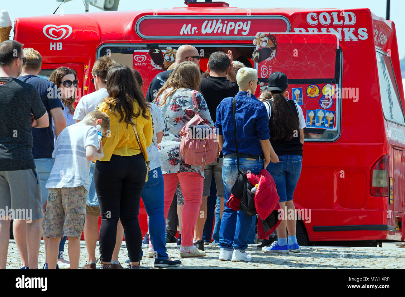 People queue for an ice cream from a Mr Whippy van during the hot weather - Stock Image