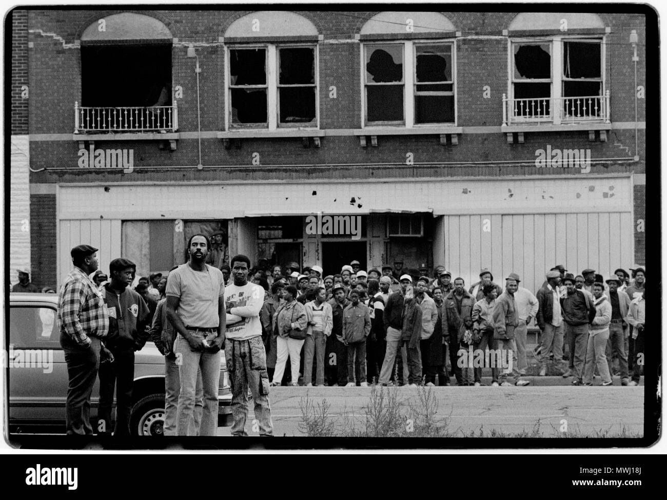 Detroit Michigan USA. 1988 Armed Policemen react to a shooting incident in the poor northern area of Detroit. The local black population watch. Detroit is a major port on the Detroit River, one of the four major straits that connect the Great Lakes system to the Saint Lawrence Seaway - Stock Image