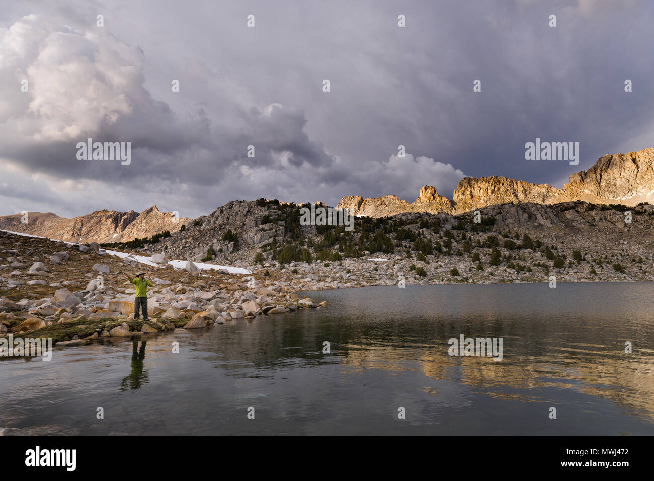Sunset fly fishing at Steelhead Lake with storm clouds in the High Sierra mountains near Pine Creek Pass and French Canyon. - Stock Image