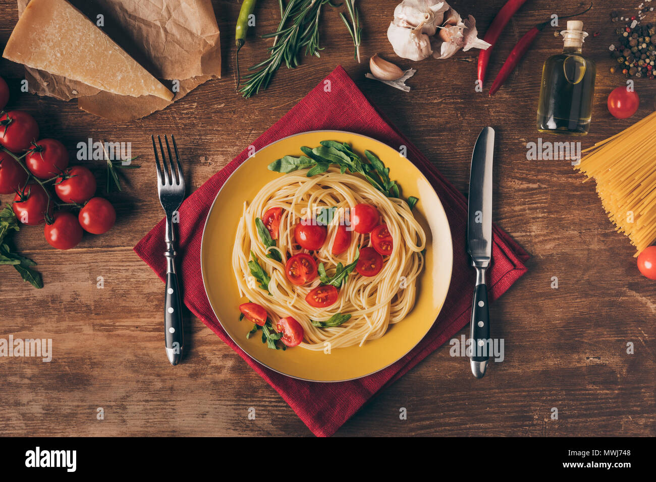 top view of traditional italian pasta with tomatoes and arugula in plate on wooden table with ingredients - Stock Image