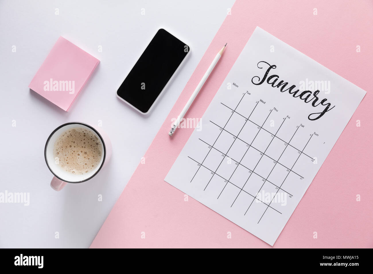 flat lay with calendar smartphone cup of coffee and blank sticky