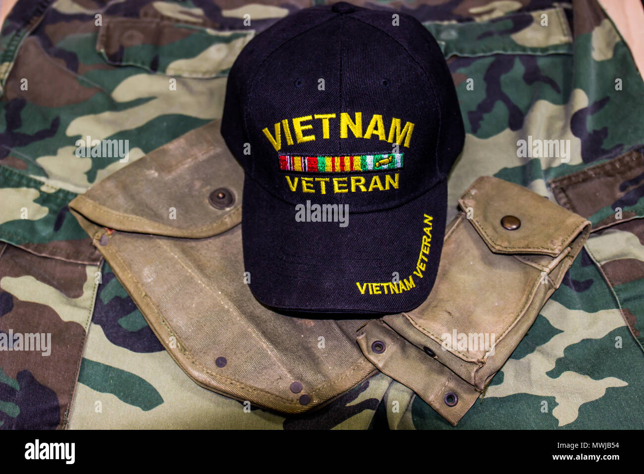 Vietnam Veteran Hat With Ammo Pouch On Camouflage Uniform - Stock Image