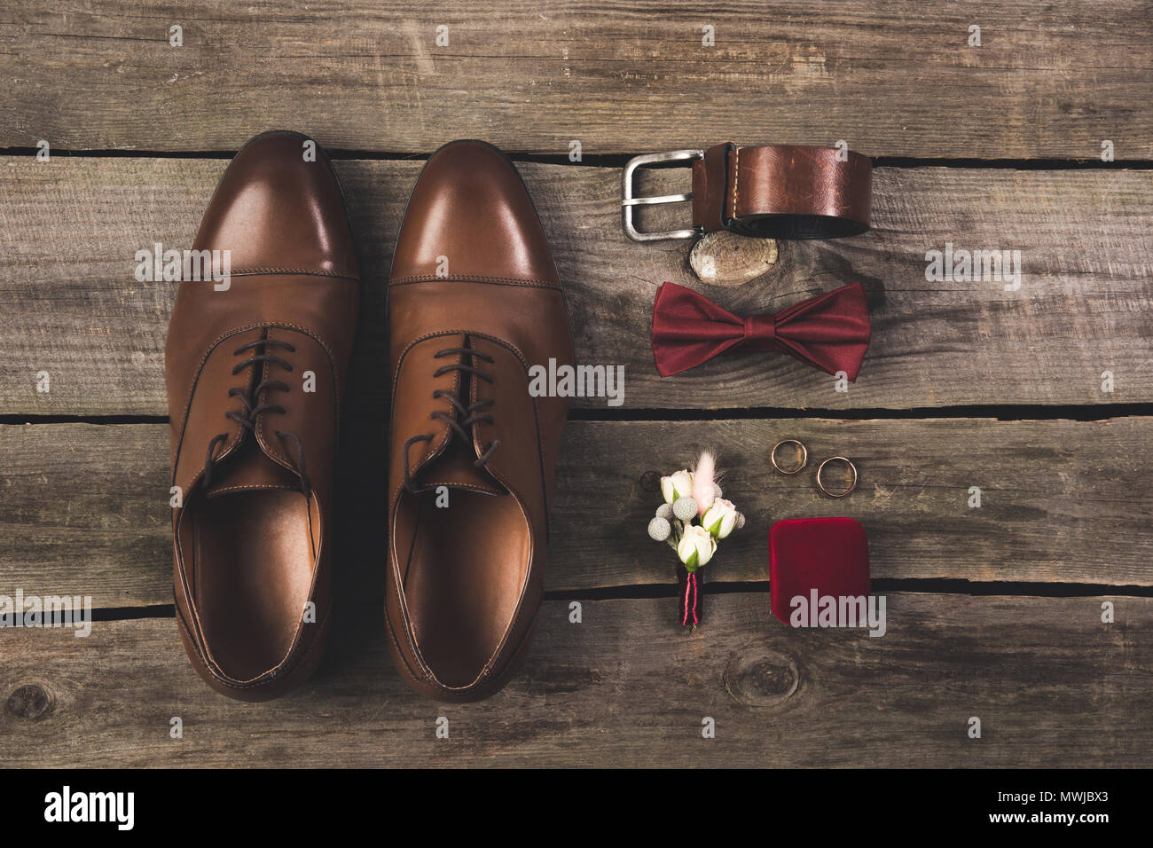 Flat lay with arranged grooms accessories and wedding rings on flat lay with arranged grooms accessories and wedding rings on wooden tabletop junglespirit Image collections