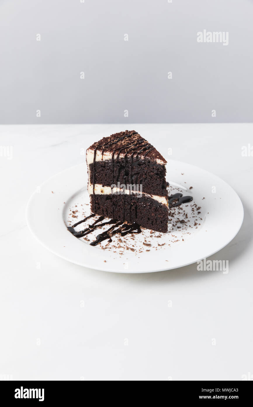 Front view of chocolate cake with glaze on plate placed on white surface - Stock Image