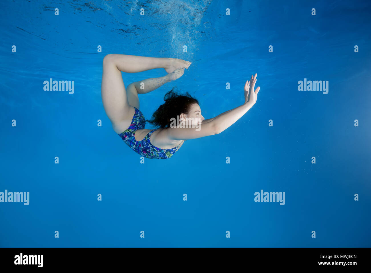 Girl curled into a wheel under water in the pool. Underwater acrobatics - Stock Image