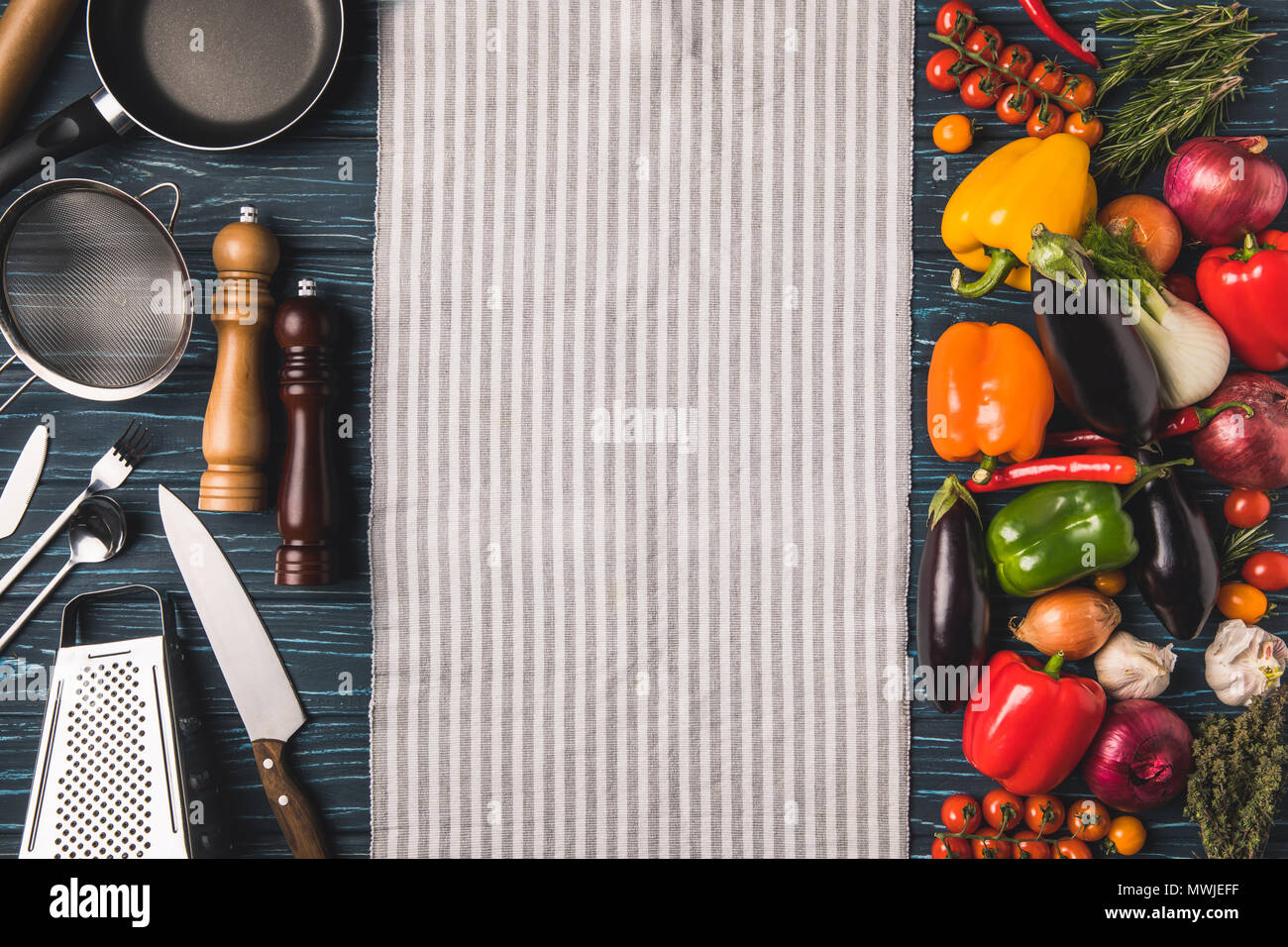 top view of utensil for cooking and vegetables on wooden table - Stock Image
