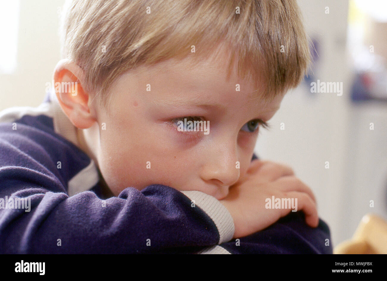 Boy aged four years old gazing into space - Stock Image