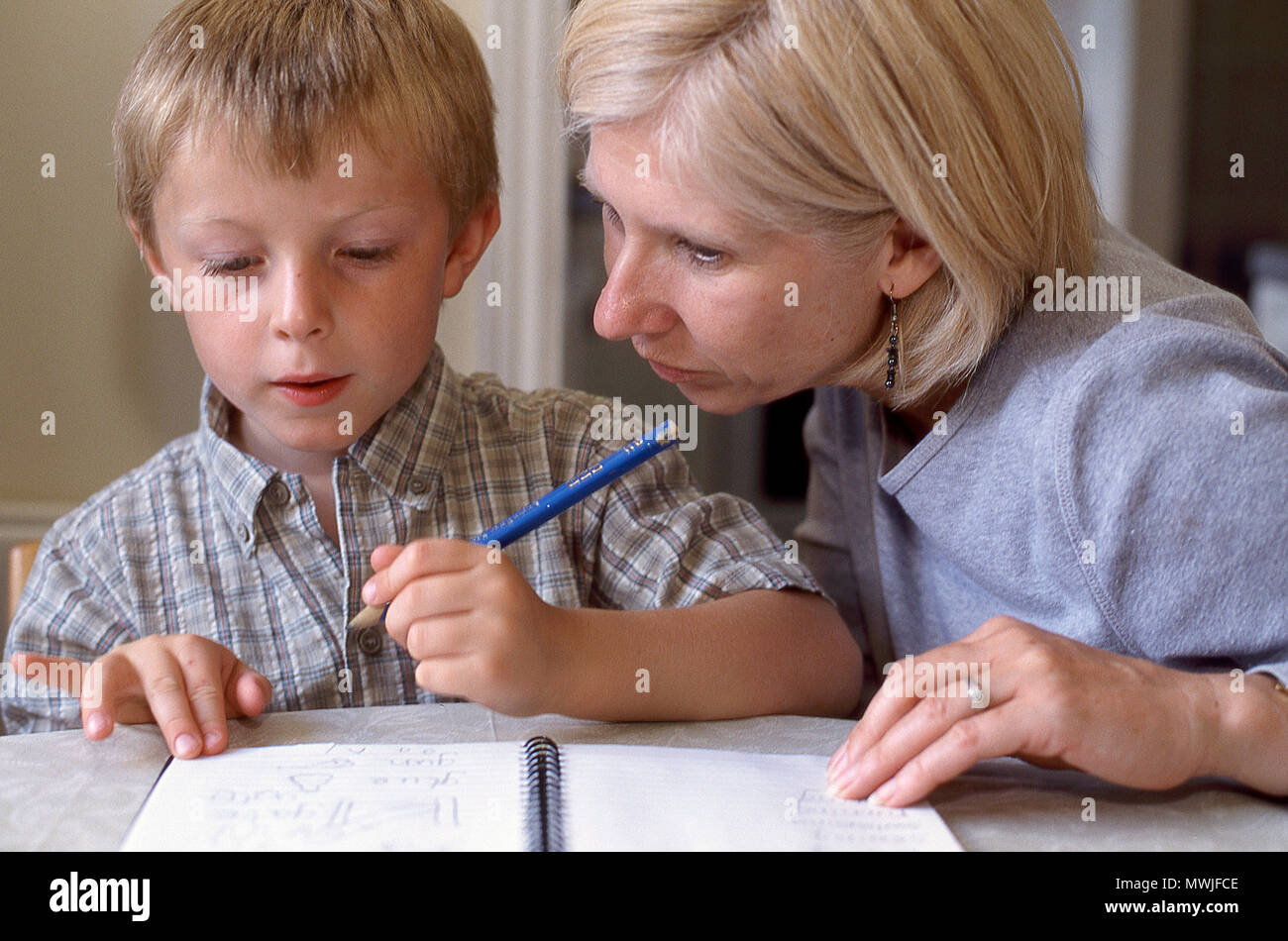Five year old boy with his mother learning to write - Stock Image