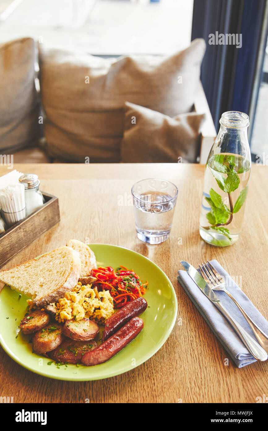 Brunch in restaurant with scramble eggs and sausage - Stock Image