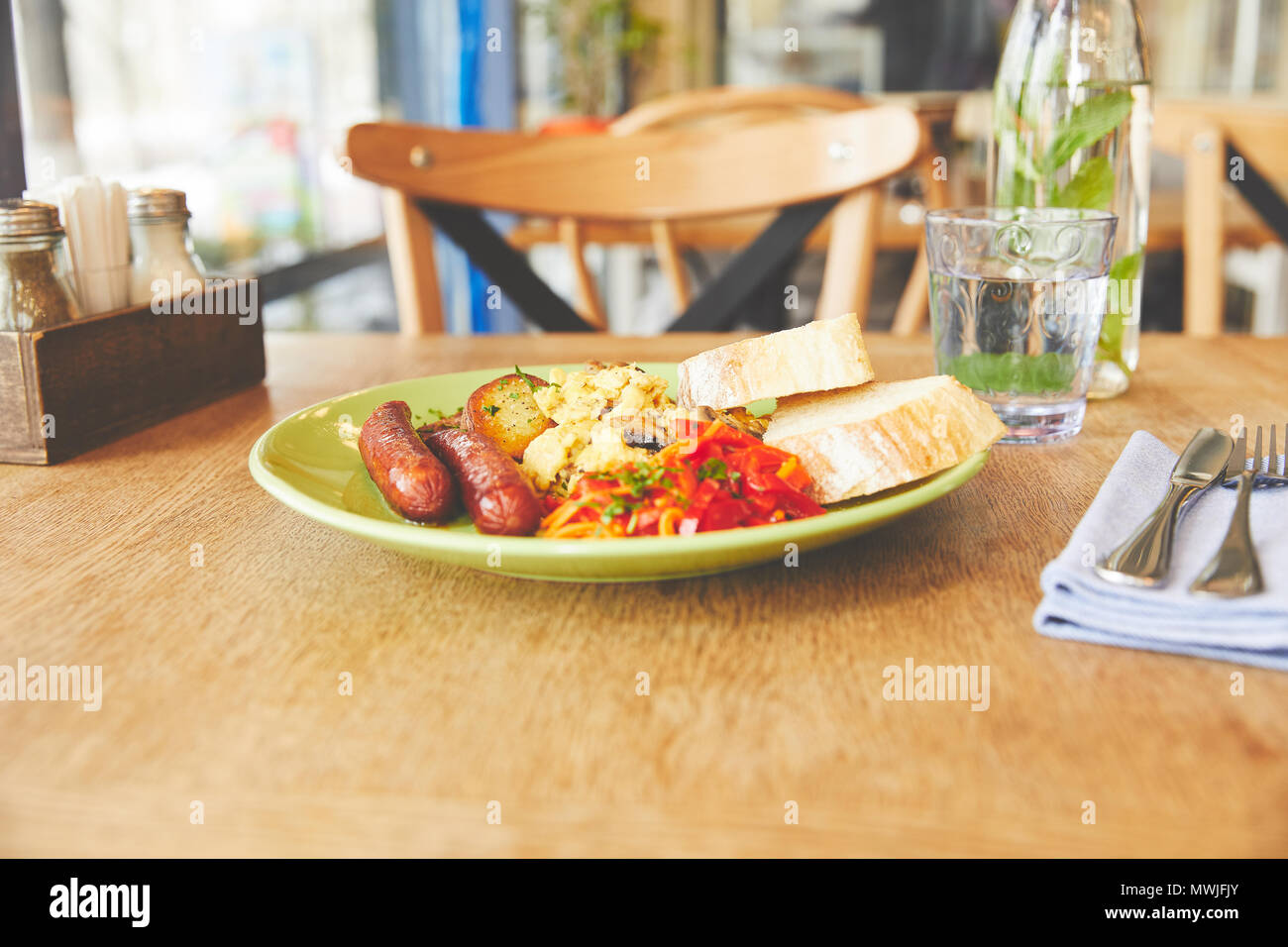 Breakfast with scramble eggs served with vegetables - Stock Image