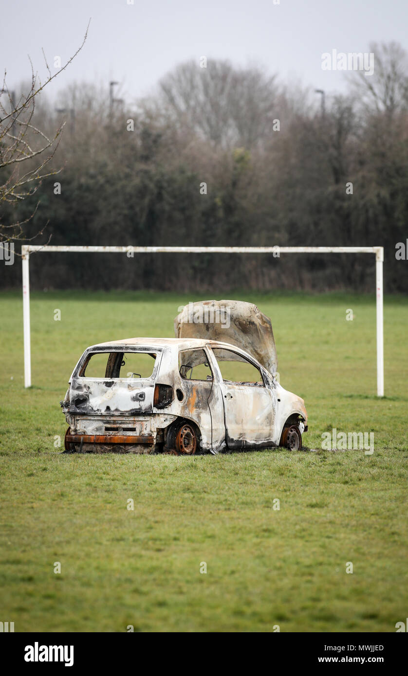 Burned Out stolen car abandoned on a community football pitch next to a council estate in Hampshire - Stock Image