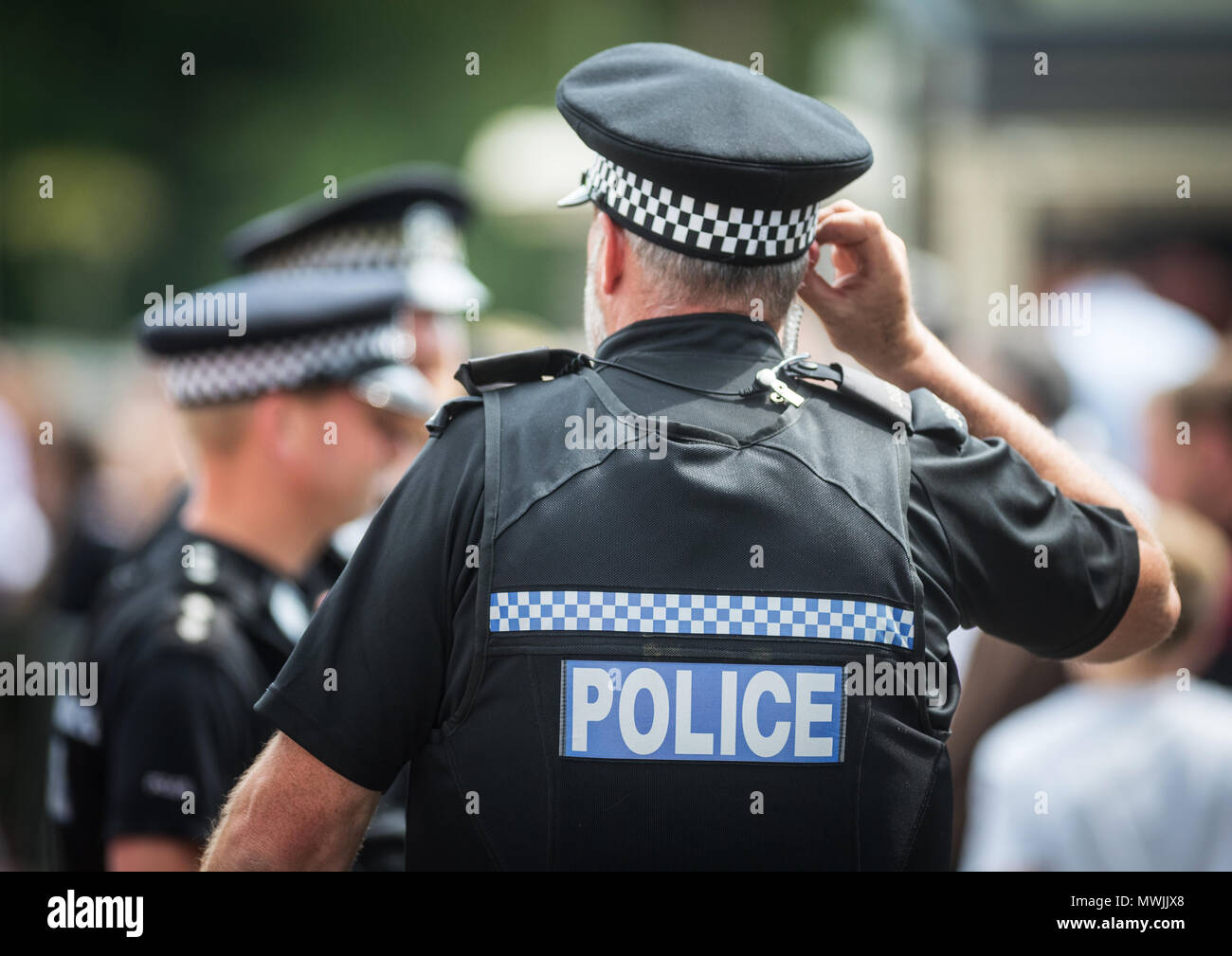 Police officers on duty at a public event in Hampshire, with a policeman listening to his police radio in his ear - Stock Image