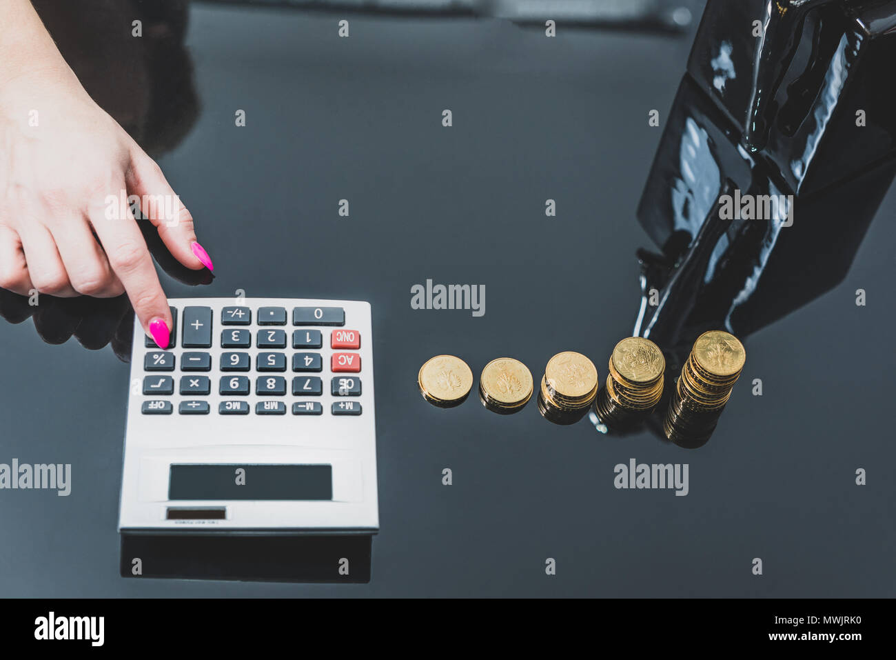 Concept of enrichment and financial growth. Gold coins. Female working hard, saving money. Income Tax Raise. Businesswoman's hand clicks into a calcul - Stock Image