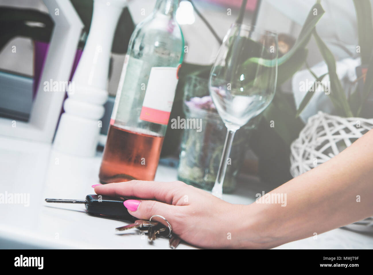 Alcohol and drinking alcohol and driving a car. I drink, I'm not driving. Irresponsibility, lack of reason. Woman holds car keys with hand, in the bac - Stock Image