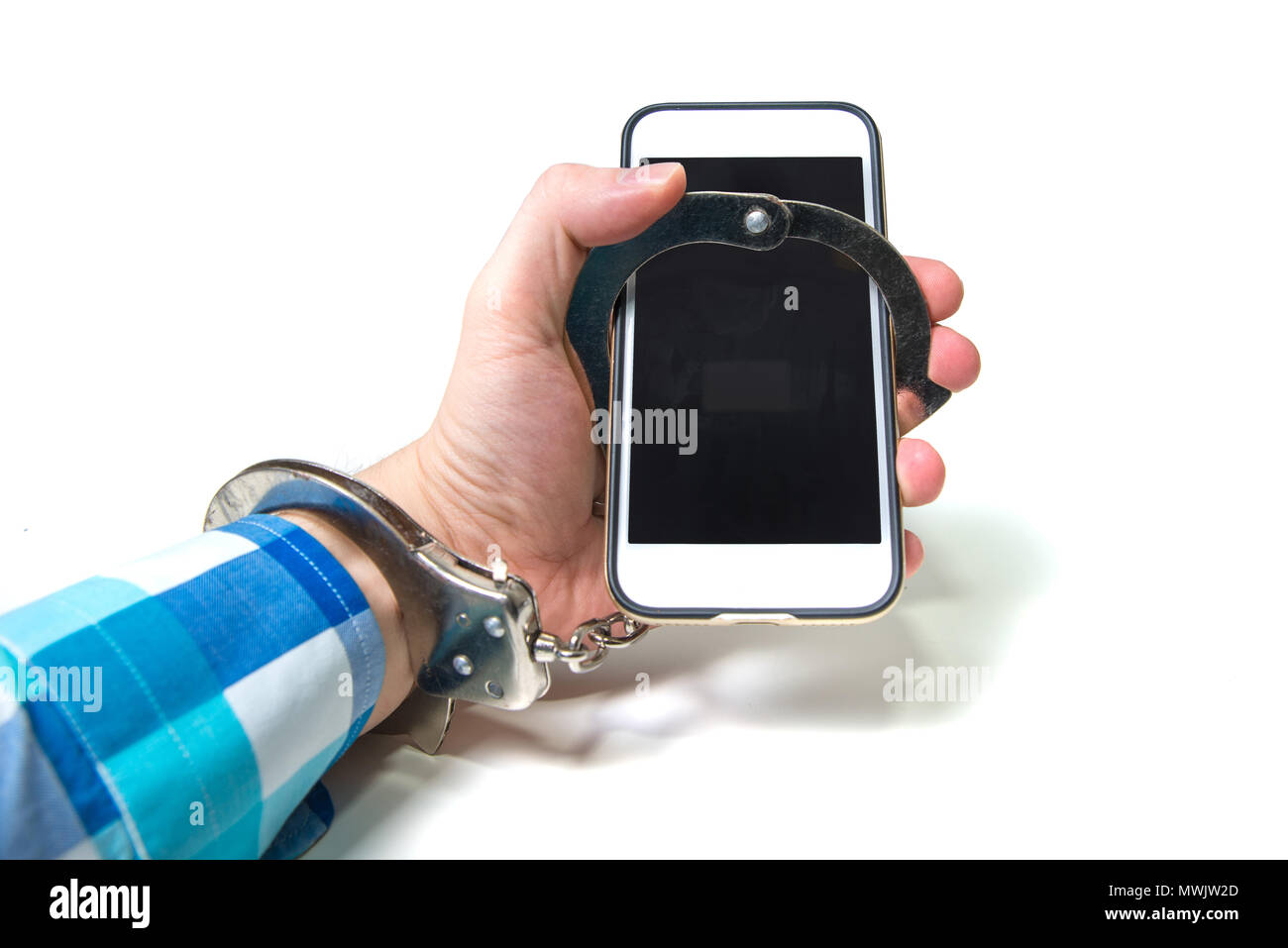 A man handcuffed to a white telephone. Addiction to the online world. The concept of human attachment to the phone. A global problem with the cyber wo - Stock Image