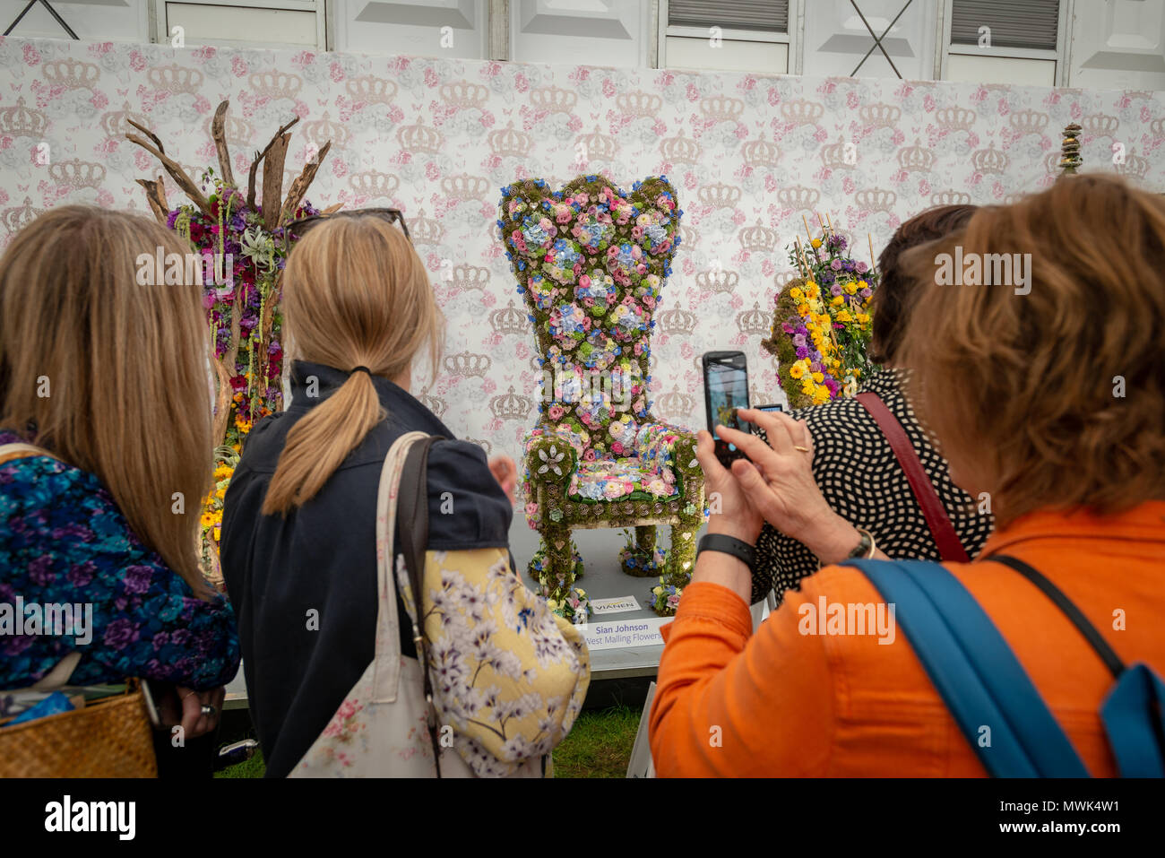 Visitors to the RHS Chelsea Flower Show take photographs of floral thrones which have been entered into the Florist Of The Year category of the show.  Stock Photo