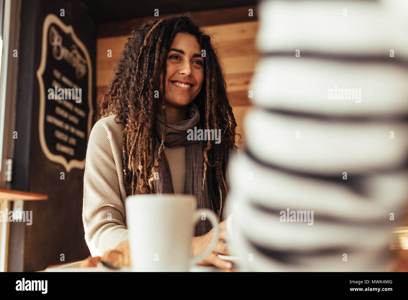Smiling woman sitting in a restaurant talking to her friend. Friends sitting at a cafe with coffee on the table. - Stock Image