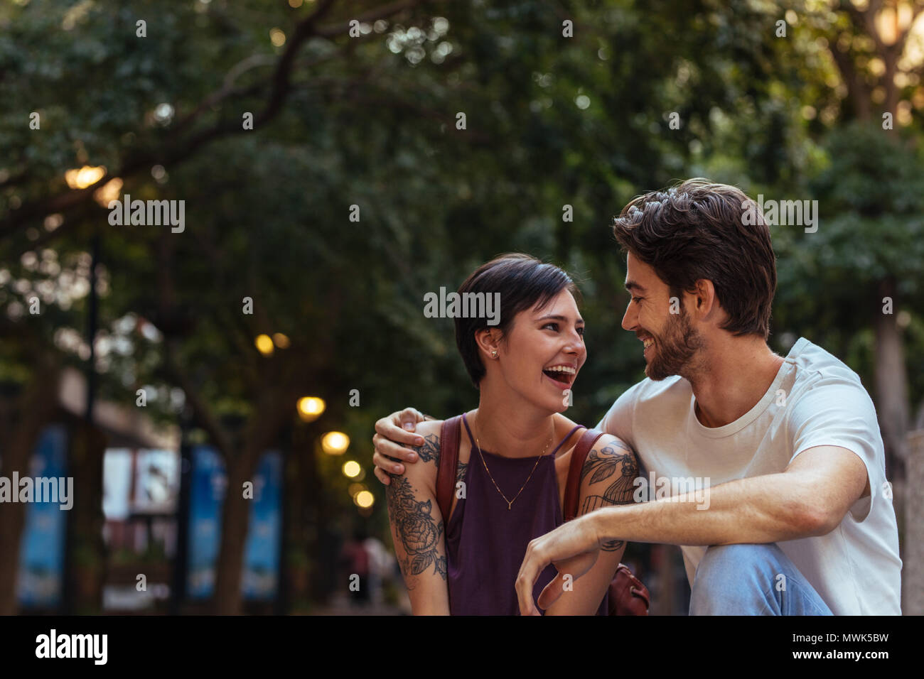 Happy explorer couple sitting outdoors and talking. Man talking to woman with his arm around her shoulders. Stock Photo