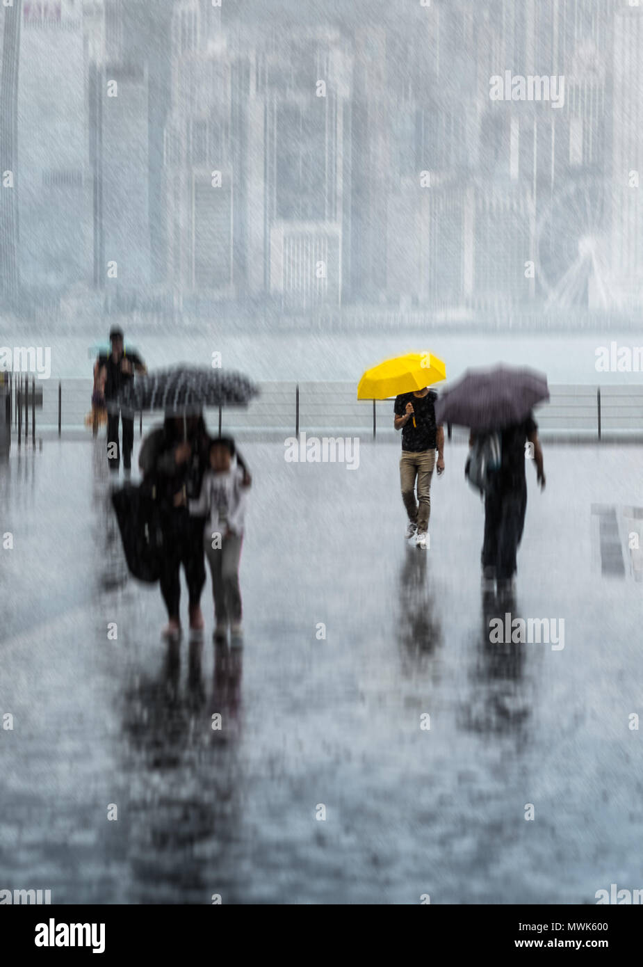Blurred people with umbrellas walking by the street under the strong rain. Hong Kong Island in haze on background. Yellow umbrella. - Stock Image
