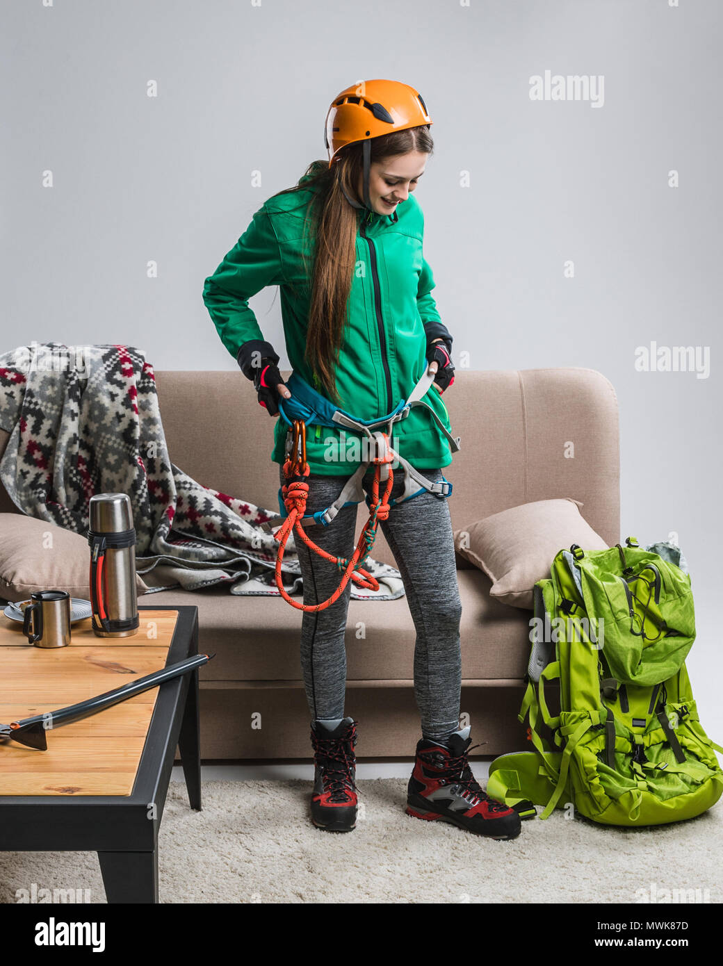 beautiful climber with climbing equipment at home - Stock Image