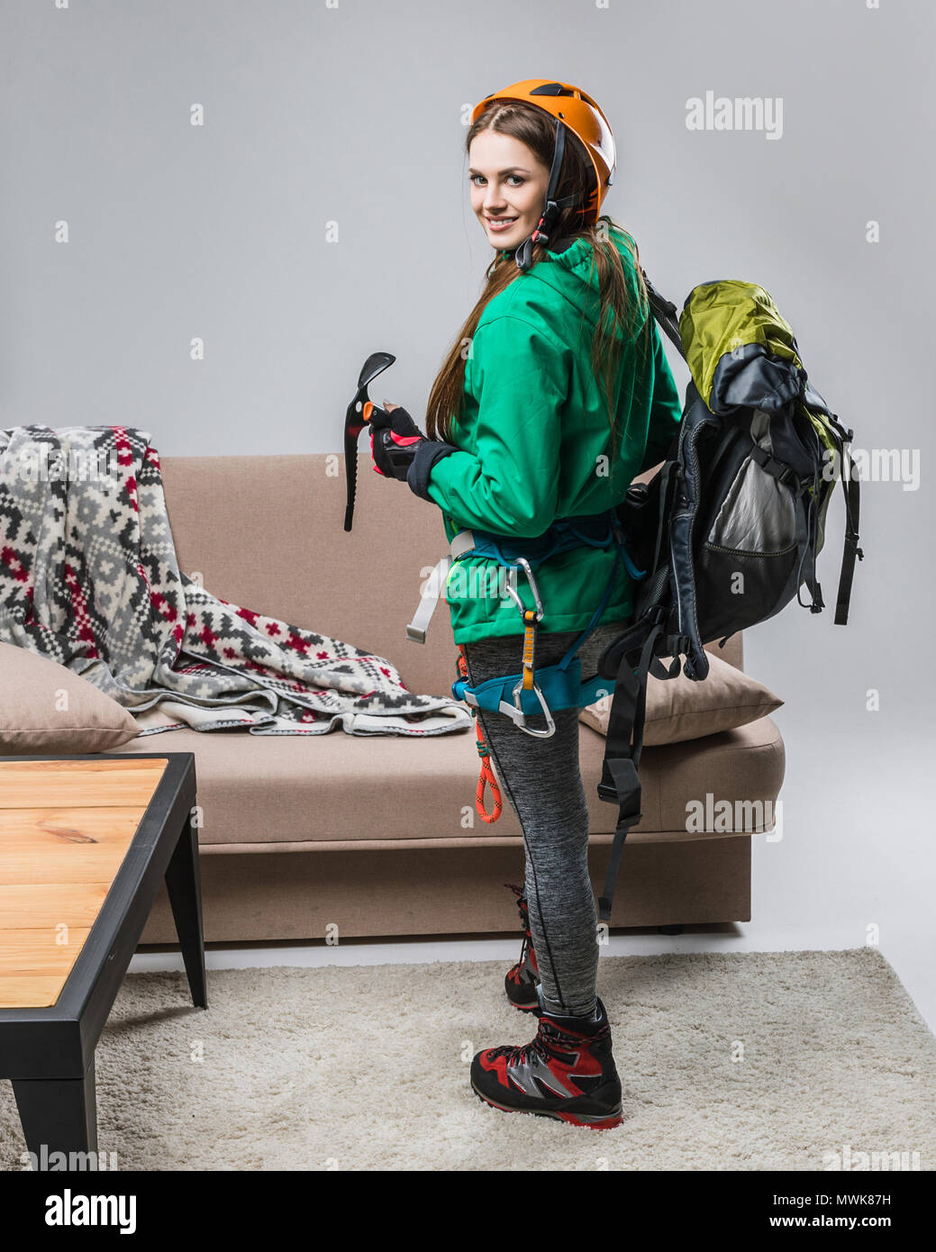 beautiful climber in helmet with climbing equipment at home - Stock Image