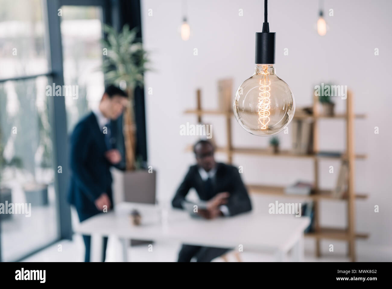vintage lamp with business colleagues sitting in modern office blurred on background - Stock Image