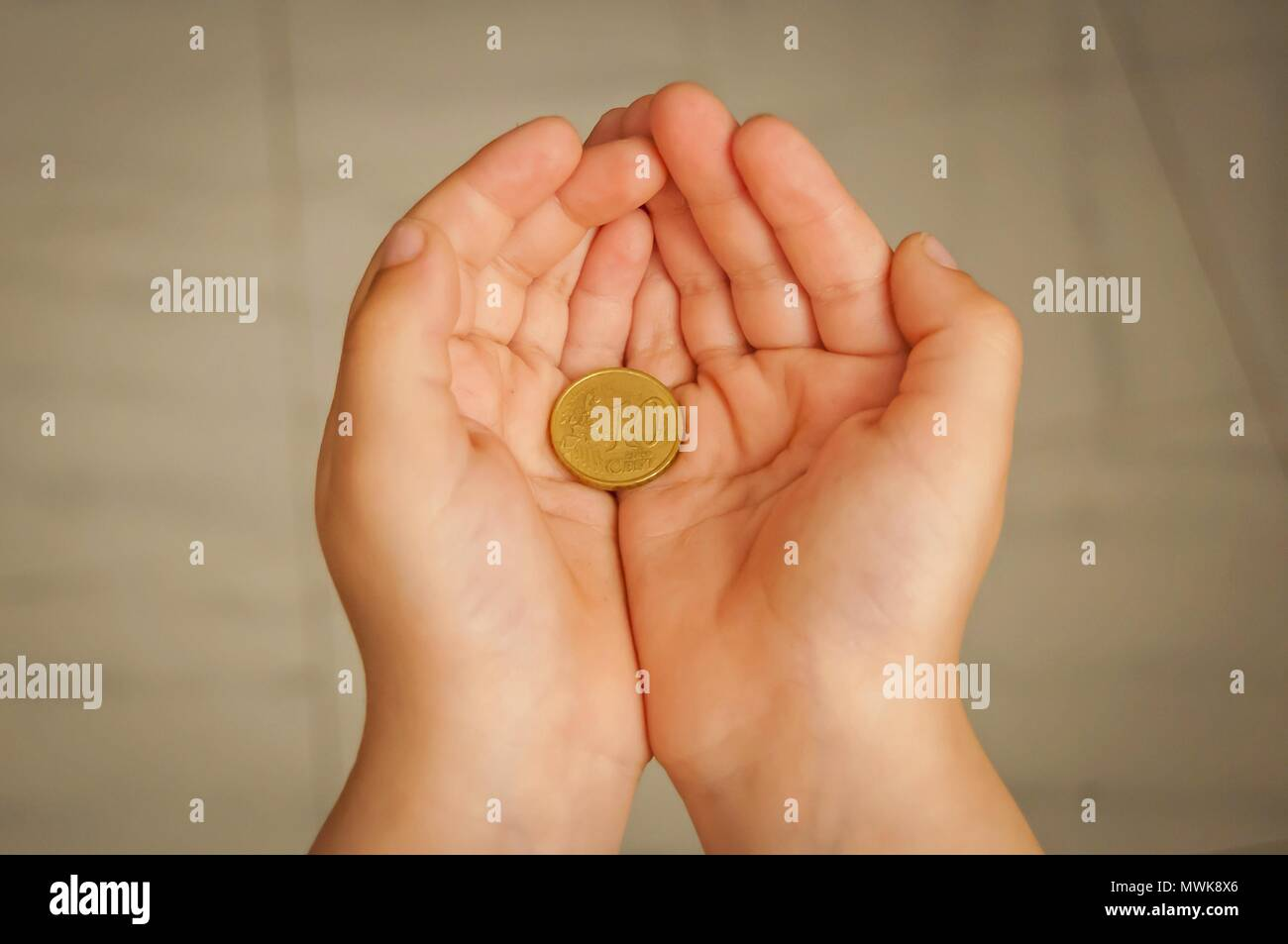 Child holding ten euro cents coin in his hands. Pocket money concept, first money earned stock image. - Stock Image