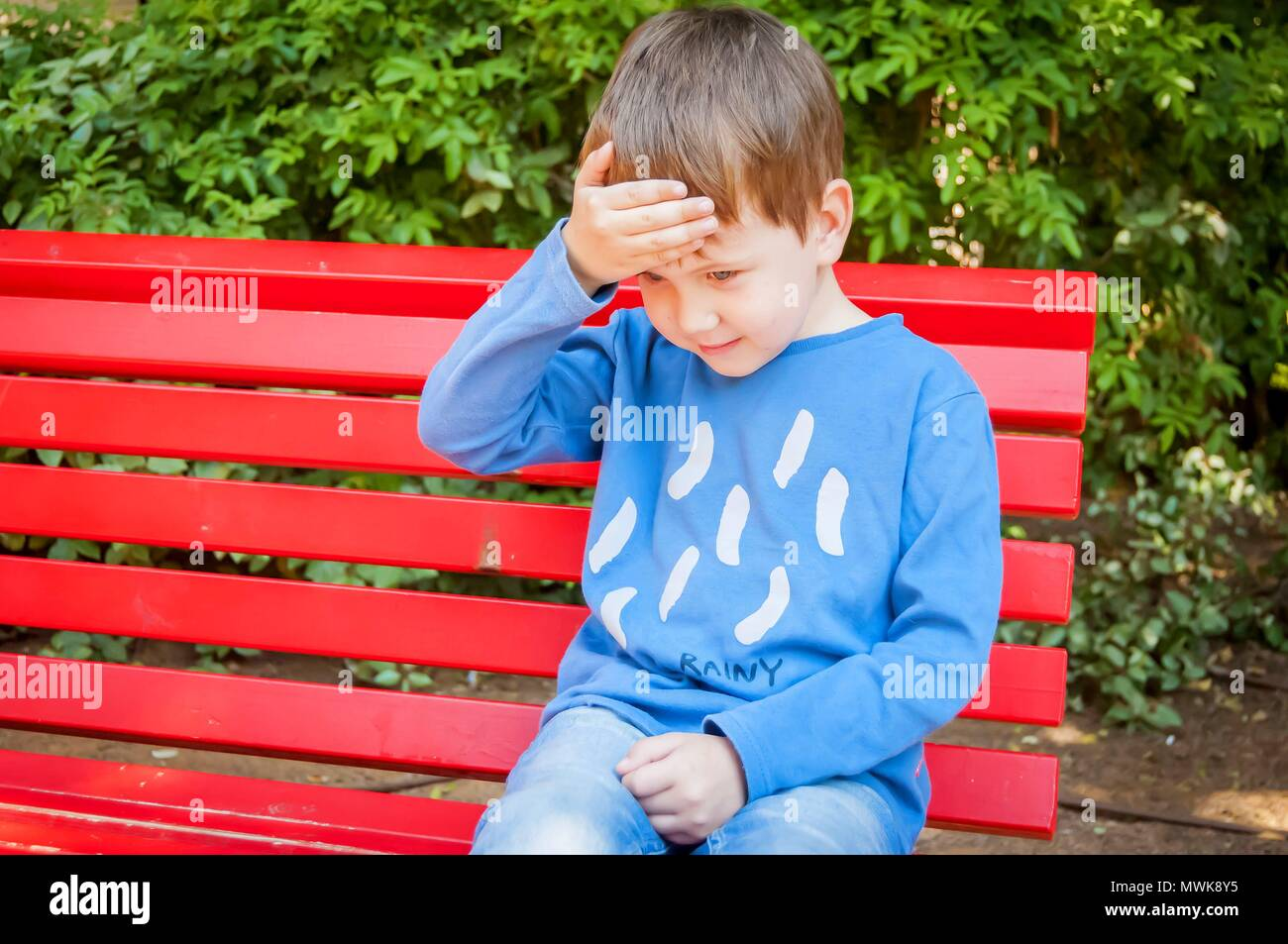Cute optimistic Caucasian child puts a hand on his forehead as if he has a head ache stock image. Grownup child - Stock Image