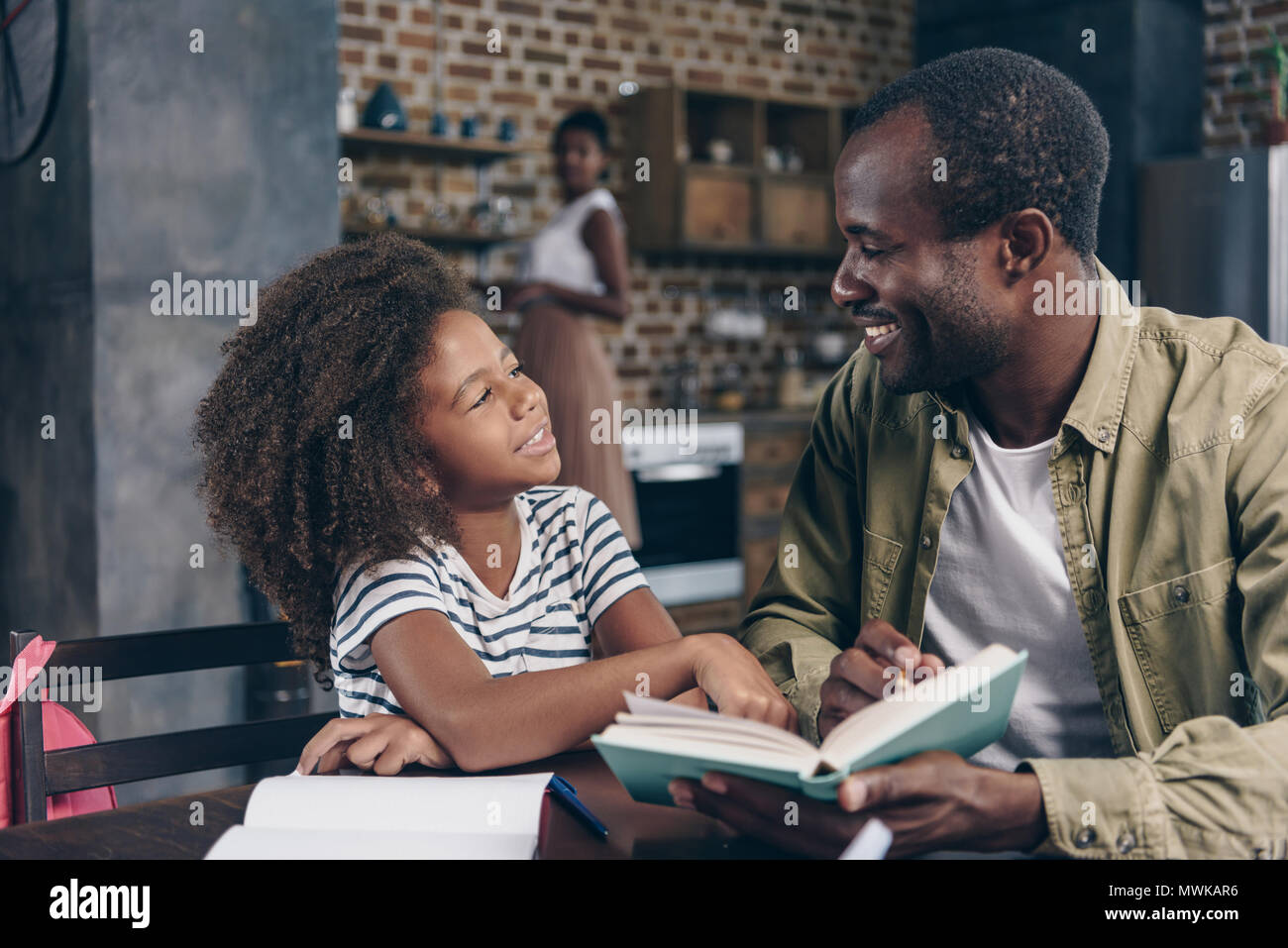 Father and daughter reading a book together at the kitchen table Stock Photo