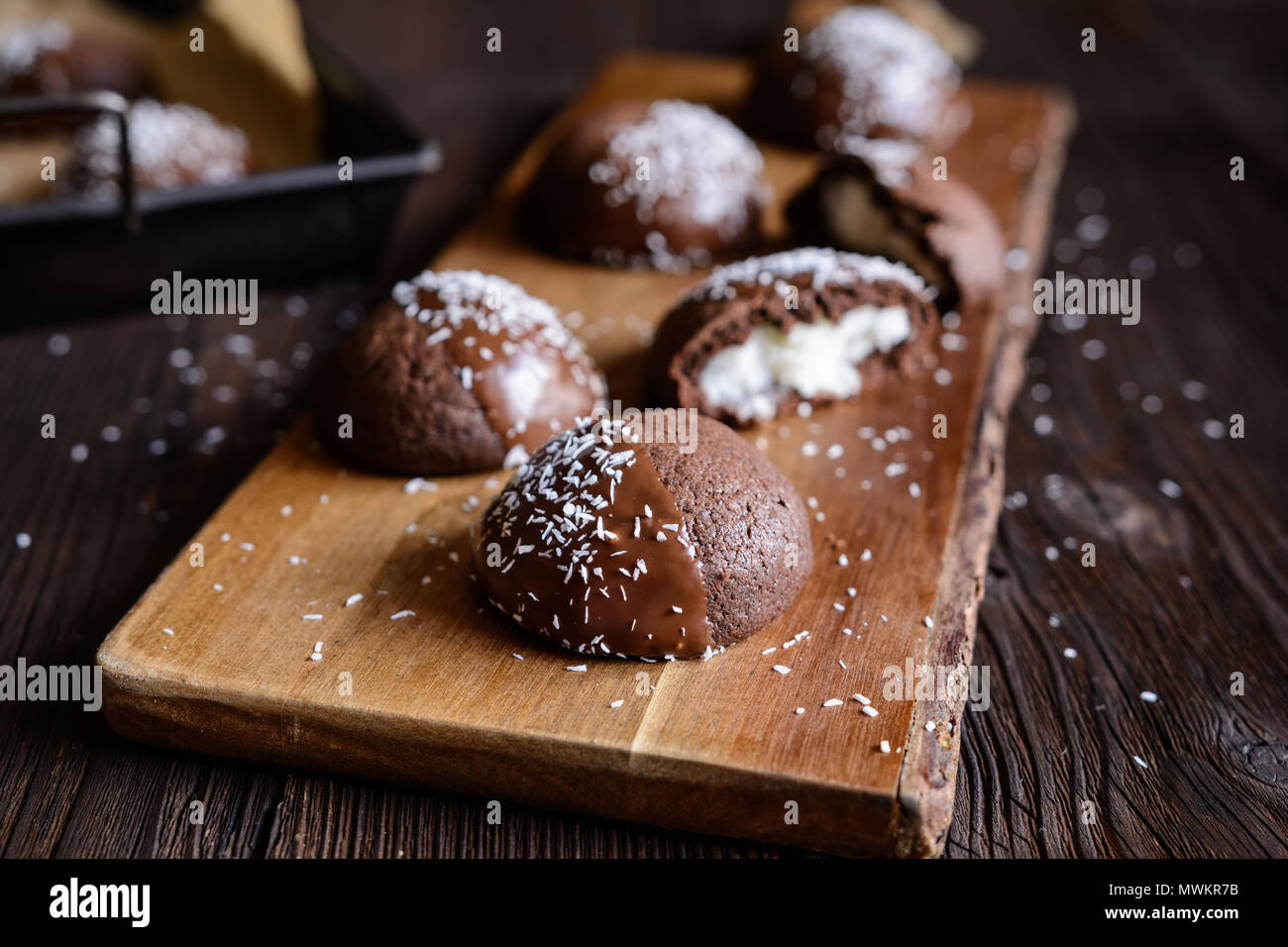 Delicious cocoa biscuits with coconut filling, decorated with chocolate and grated coconut - Stock Image