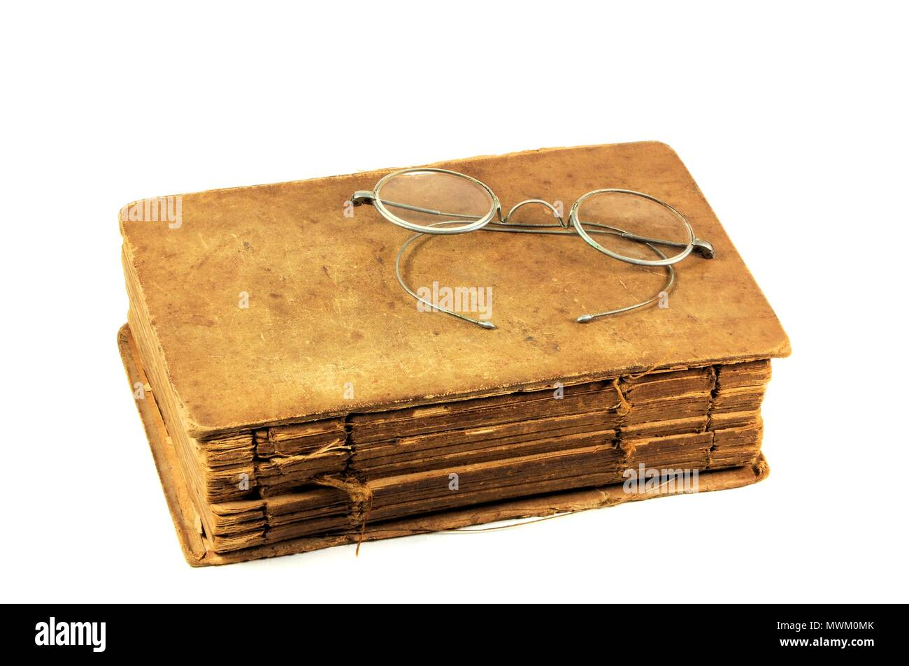 149f3e593ae Very old and worn book with antique round eyeglasses. Isolated on white  background.