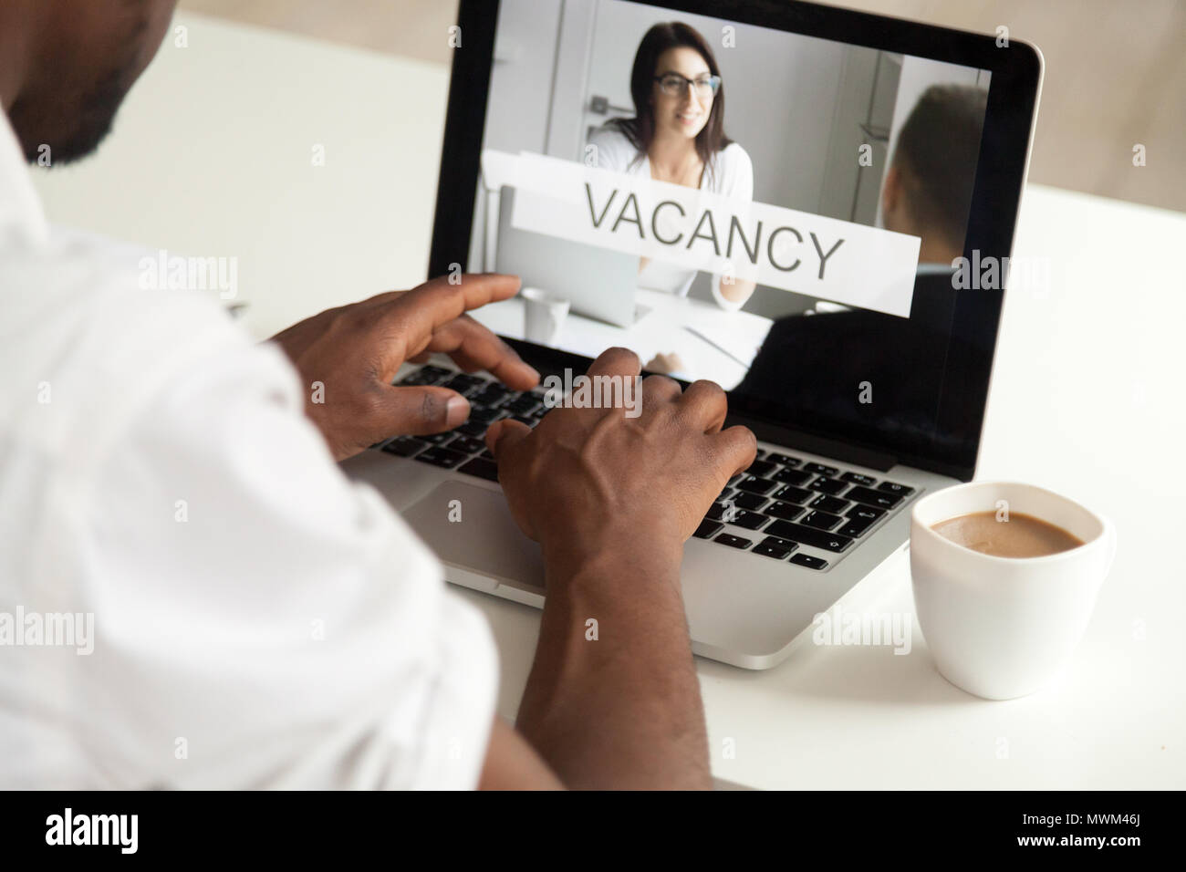 Close up of black man replying to open job position online - Stock Image