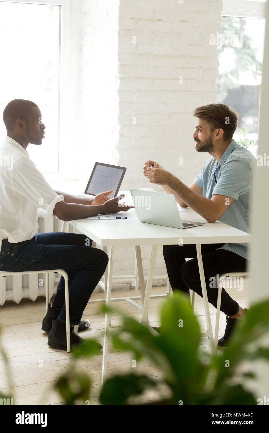 Multiethnic team talking about business issues  - Stock Image