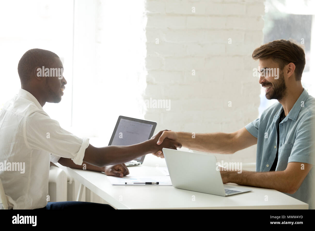 Business partners shaking hands greeting each other Stock Photo