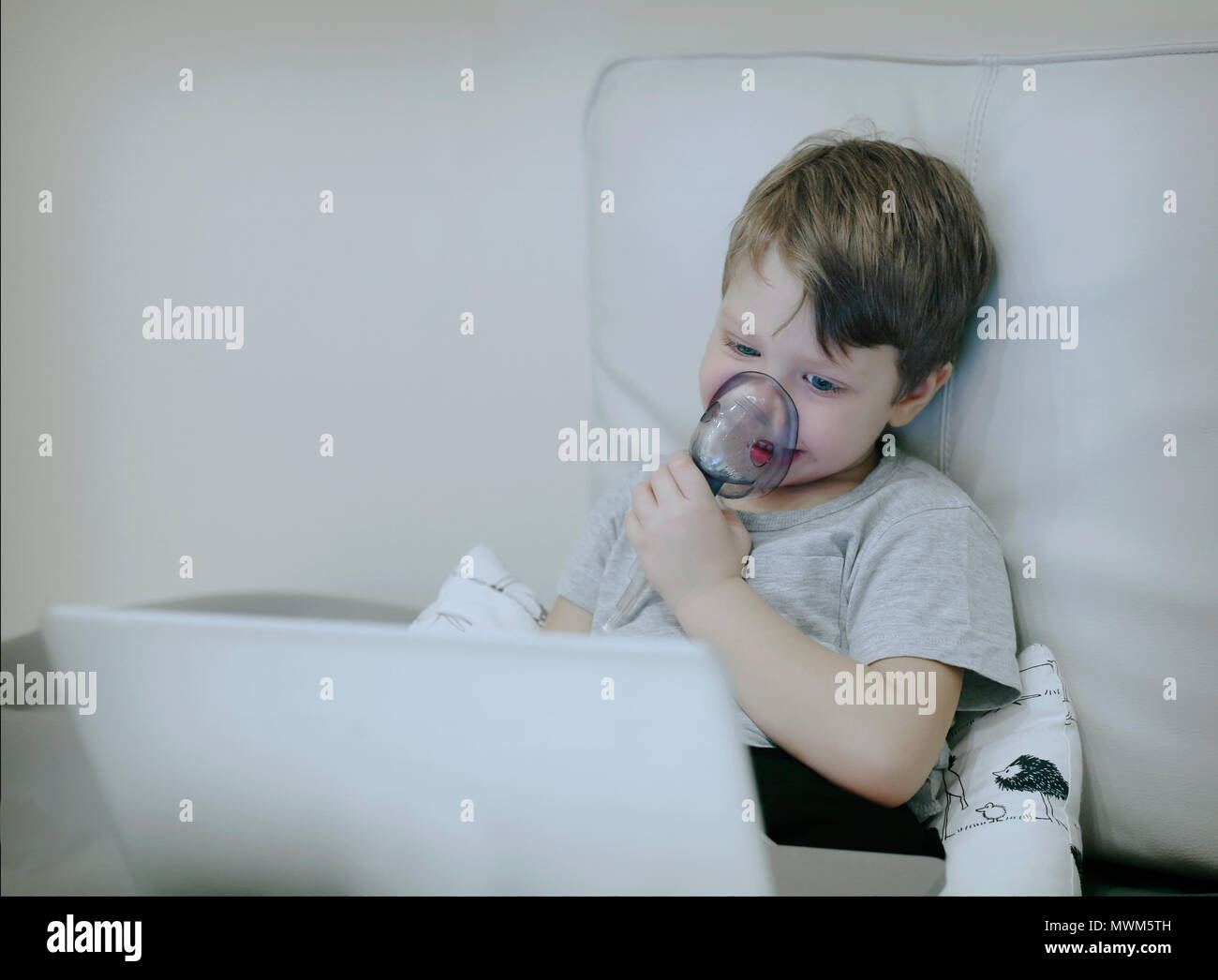 Smiling chid with pediatric nebulizer mask looking at laptop scr - Stock Image