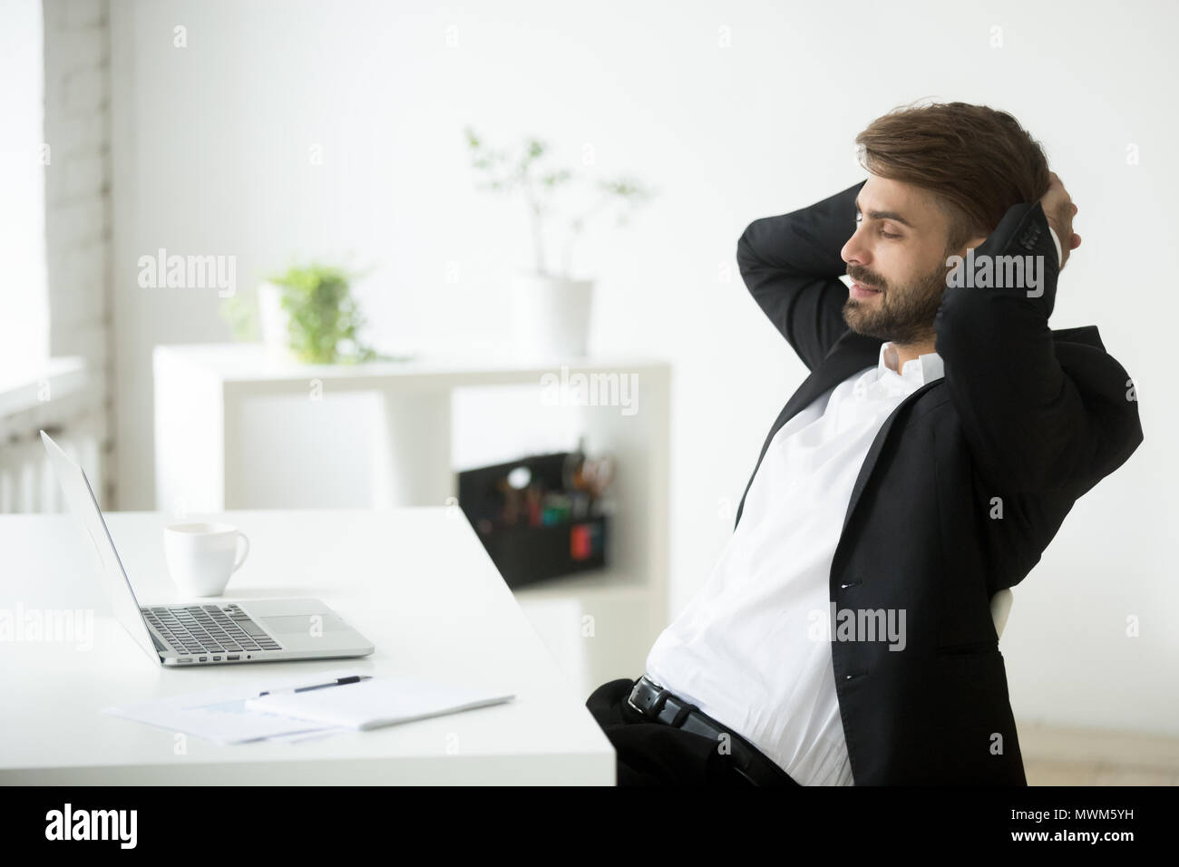 Satisfied businessman relaxing leaning back in chair - Stock Image
