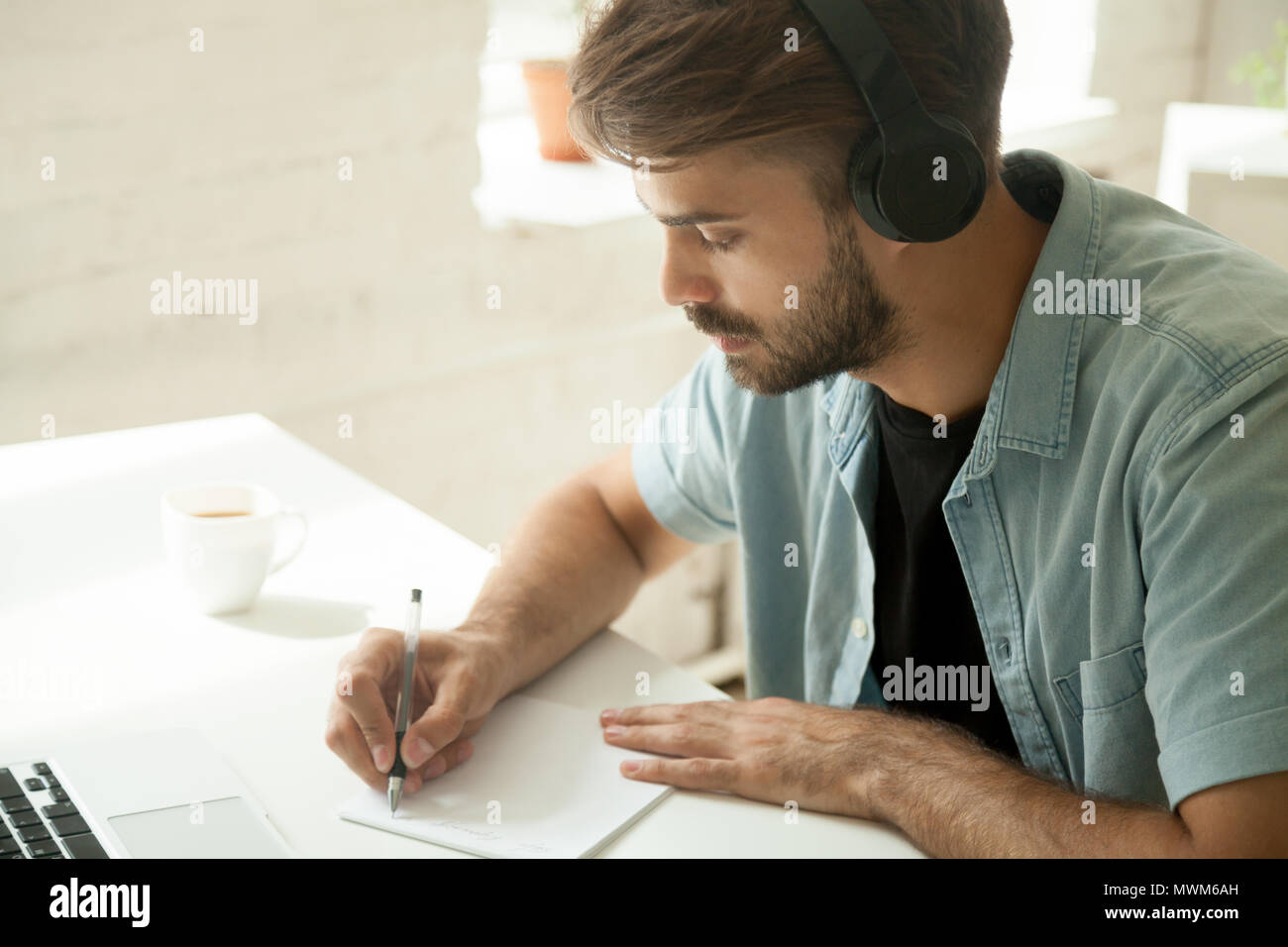 Concentrated worker in headphones watching webinar noting import - Stock Image