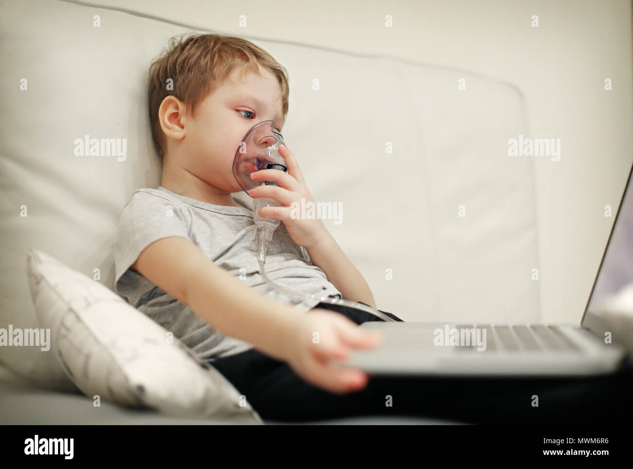 Sick chid with pediatric nebulizer mask in front of laptop. - Stock Image