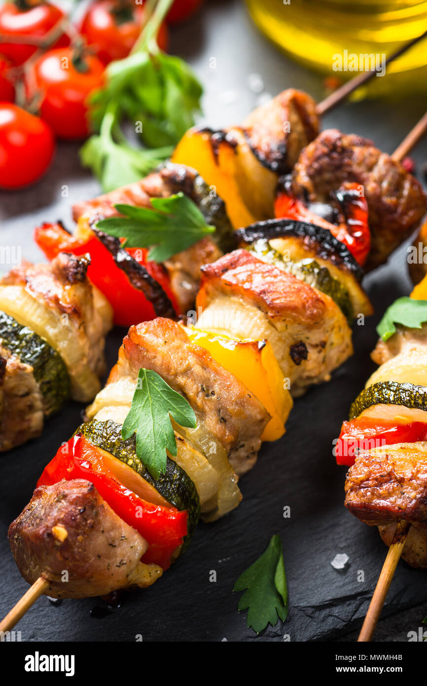 Grilled shish kebab or shashlik with vegetables  on black stone table. Pork meat. Barbeque meat dish. - Stock Image