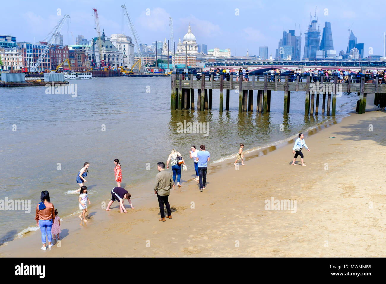 People enjoying the sandy beach of River Thames foreshore at low tide. - Stock Image