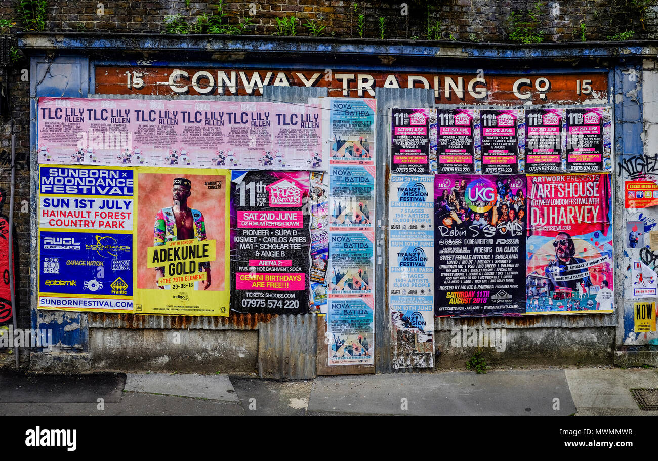 Fly posters covering facade of derelict shop in east London street, UK - Stock Image