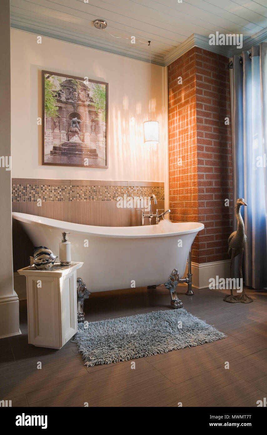 White porcelain claw foot bathtub in the main bathroom inside an old 1877 cottage style residential home - Stock Image