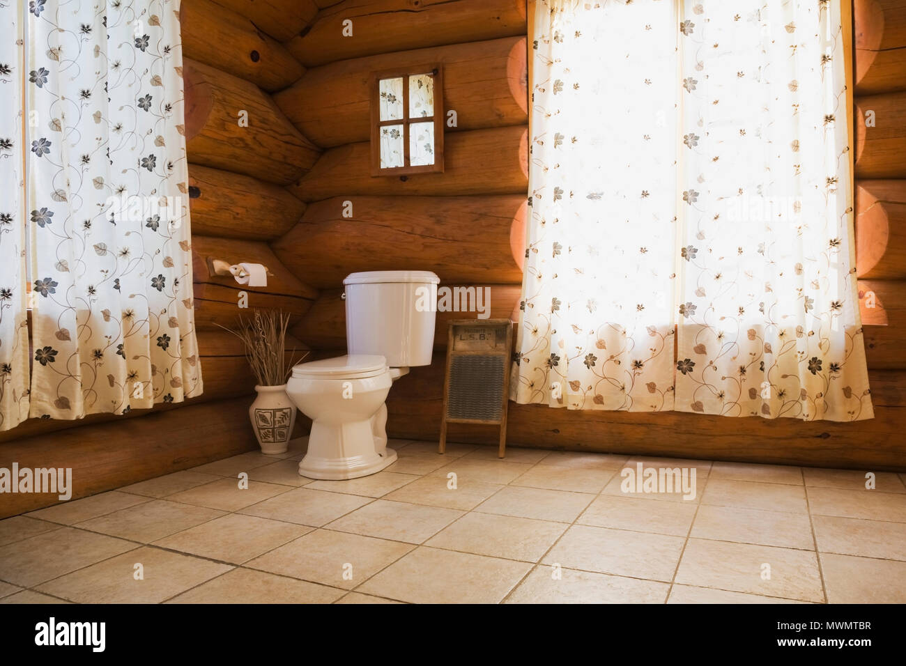 Toilet in corner of main bathroom inside a cottage style log home ...